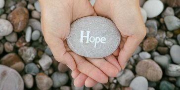 Woman holding stone with the word Hope